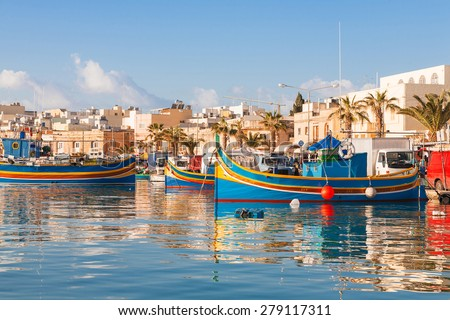 Colorful typical boats - Mediterranean traditional fisherman village in the south east of Malta. Early winter morning in Marsaxlokk, Malta. - stock photo