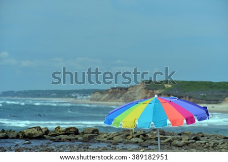 colorful umbrella Ditch Plains surf beach Montauk, Long Island, The Hamptons, New York with dunes in background