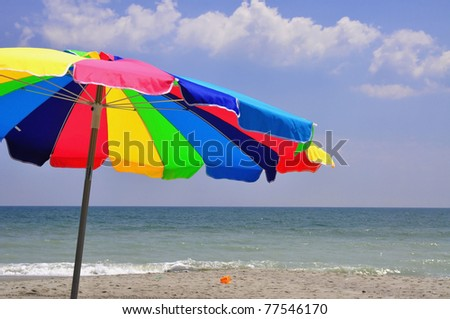 Colorful umbrella on a Summer day at the beach - stock photo