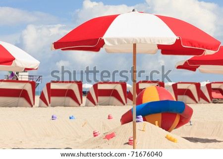 Colorful umbrellas and lounge chairs in the trendy and popular South Beach in Miami. - stock photo