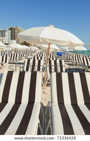 Colorful umbrellas and lounge chairs on Miami's South Beach. - stock photo