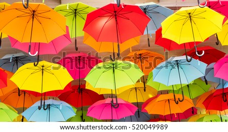 Colorful umbrellas hanging from a roof, creating an interesting abstract background.
