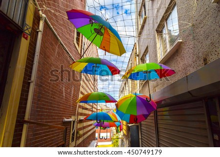 Colorful umbrellas hanging over the street with blue sky - stock photo