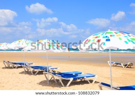 Colorful umbrellas on Mediterranean sandy sea beach - stock photo