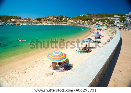 Colorful umbrellas on Puerto de Soller, Port of Mallorca island in balearic islands, Spain. Beautiful picture of people resting on the beach on bright summer day. - stock photo