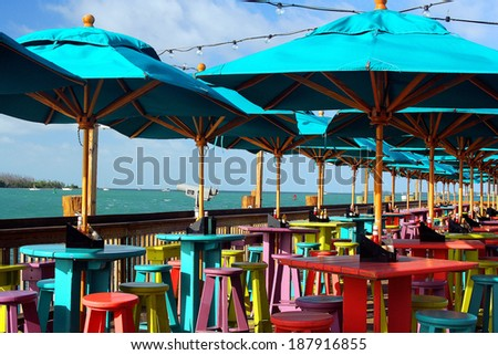 Colorful Umbrellas, Tables And Chairs By The Sea