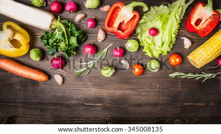 Colorful various of organic farm vegetables peppers, carrots, daikon, lettuce, radishes, corn, rosemary border ,place for text on wooden rustic background top view