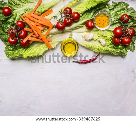 Colorful various of organic farm vegetables tomatoes on a branch, lettuce, sliced carrots, oil, seasonings border, place for text  on wooden rustic background top view vegetarian concept - stock photo