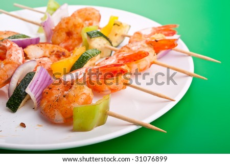 colorful vegetable and shrimp grilled kebabs on green background