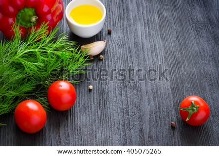colorful vegetables, olive oil and spices on a dark background, space for text