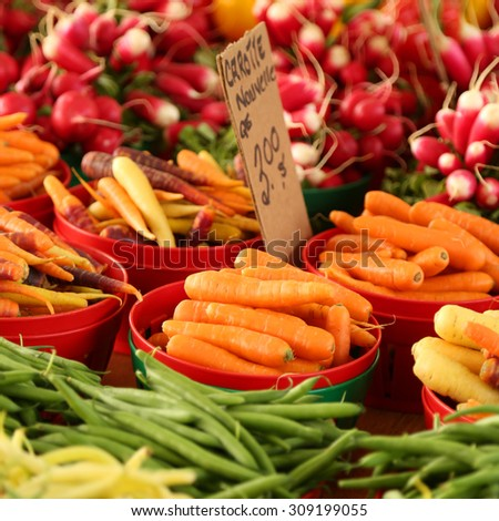 Colorful vegetables on a display in a market.  Focus is on the carrots only. - stock photo