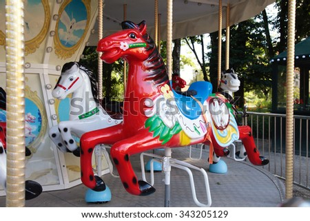 Colorful vintage carousel in a summer park. Merry-go-round with horses. Selective focus - stock photo