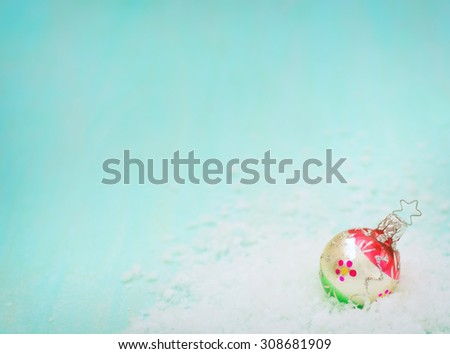 Colorful Vintage Red, Silver and Green Glass Christmas Ornament in Snow in lower corner on Rustic Cyan Grainy Painted Wood Board Background with room or space for copy, text, your words.  Horizontal  - stock photo