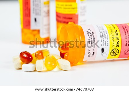 Colorful vitamins spilling from prescription bottle with warnings - stock photo