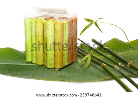 Colorful waffle rolls packed in transparent plastic bag on a leaf with bamboo sticks - stock photo
