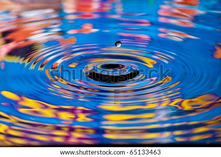 Colorful water drop photo with ripples in the water - stock photo