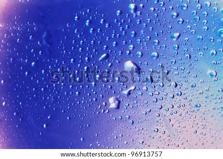 colorful water drops - blue and purple tones - close up - stock photo