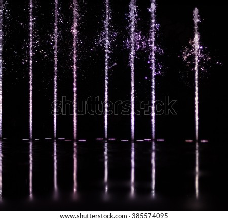 colorful water shape on fountain with black background - stock photo