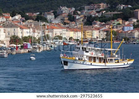colorful waterfront in small port town of Mali Losinj on the Croatian island of Veli Losinj; lively sea traffic with many boats in background and small tourist cruiser in front