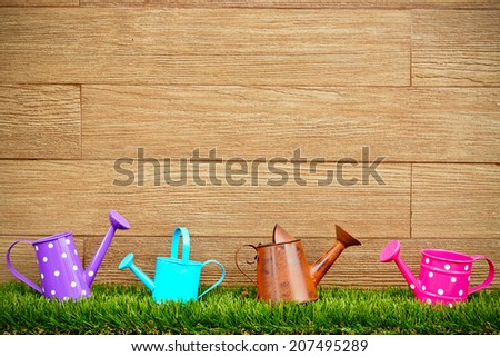 colorful watering cans on green grass with wood background - stock photo