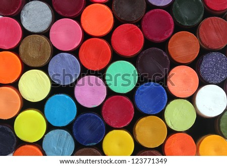 Colorful wax crayon pencils for school art arranged in rows and columns to display their vivid and bright colors - stock photo