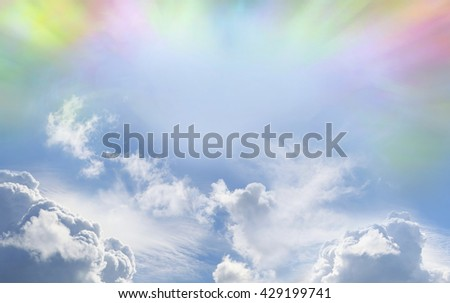 Colorful Weather phenomenon -   blue sky with various different fluffy clouds and shafts of pink, yellow, green and orange light radiating around the top with copy space in the middle - stock photo