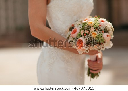 Colorful wedding bouquet in the hands of the bride