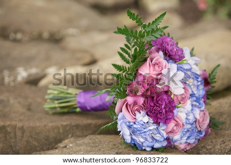 Colorful wedding bouquet outside on stone background - stock photo