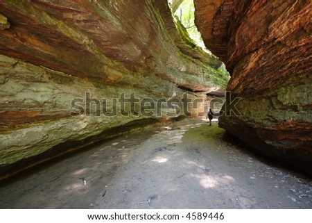 Colorful west central Indiana (USA) sandstone rock formation, lone hiker walking in distance - stock photo