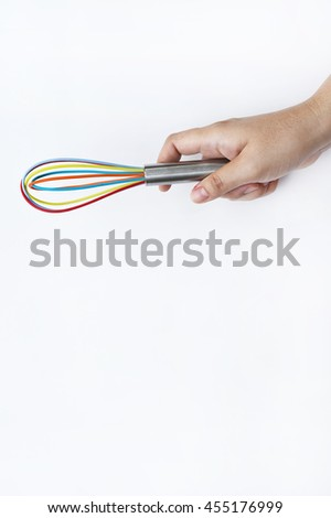 colorful whisk on hand - stock photo