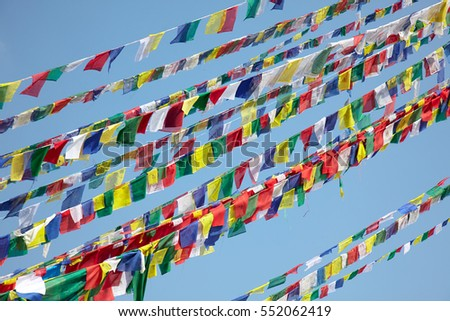 Colorful (white, blue, yellow, green and red) prayer flags over blue sky background. Buddhism prayers printed on prayer flags