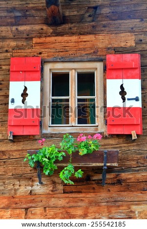 Colorful window on traditional wooden wall in Tirol, Austria - stock photo