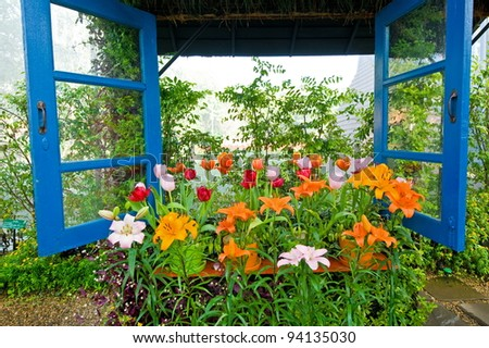 Colorful windows with tulips in the window-sill - stock photo