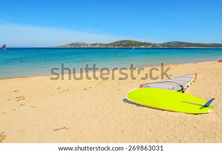colorful windsurf board on a golden beach - stock photo