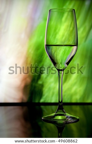 Colorful wine glass with bubble stem and glasses in soft focus in background - stock photo