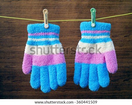 colorful winter gloves hanging on a clothes line rope with wooden background
