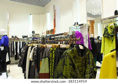Colorful women's dresses on hangers in a retail shop. Fashion and shopping concept. interior of brand new fashion clothes store - stock photo