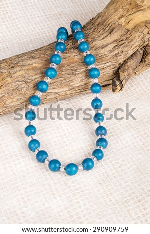 Colorful Wood Beads Necklace Over a Tree Branch Shot in Studio - stock photo