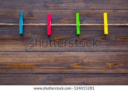 colorful wood cloth peg and hemp rope on brown plank background