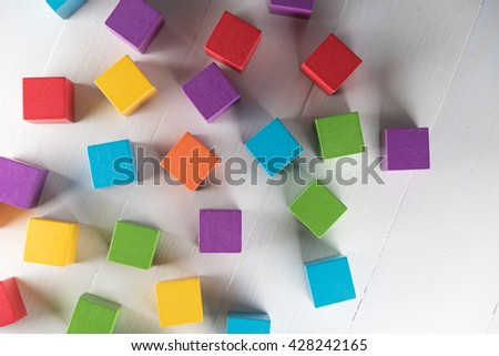 Colorful wood cube building blocks on white wood floor
