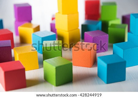 Colorful wood cube building blocks on white wood floor - stock photo