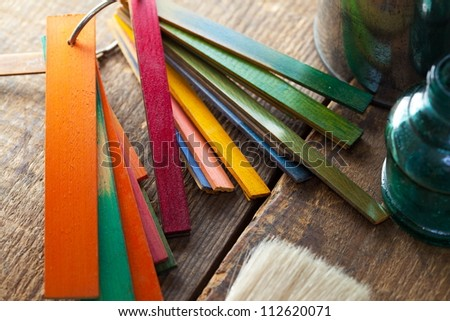 Colorful wood stain or dye color test samples, on rough wood surface. Shallow depth of field. - stock photo