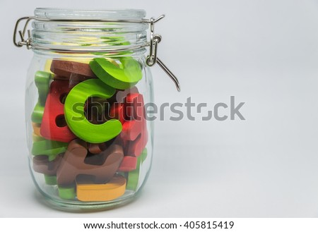 Colorful Wooden alphabet in the closed glass bottle with white background in Horizontal view and selective focus - stock photo