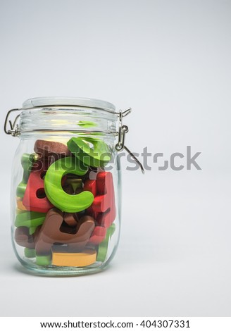 Colorful Wooden alphabet in the closed glass bottle with white background in Vertical view and selective focus - stock photo