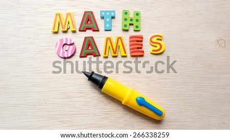 Colorful wooden alphabet letter set with cute pen and text MATH GAMES. Concept of fun preschool or back to school. Shot with natural light. Slightly defocused and close-up shot. Copy space.