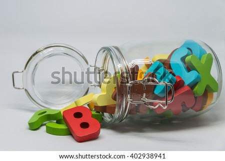 Colorful Wooden alphabet over the glass bottle with white background in Horizontal view and selective focus - stock photo