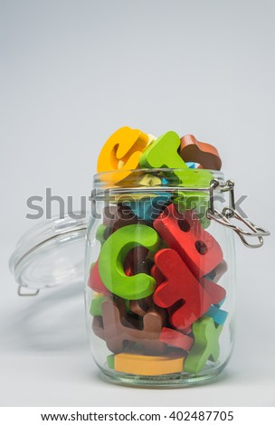 Colorful Wooden alphabet over the glass bottle with white background in Vertical view and selective focus - stock photo