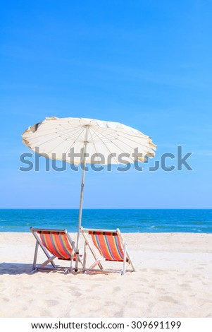 Colorful wooden beach chairs with sun umbrella - stock photo