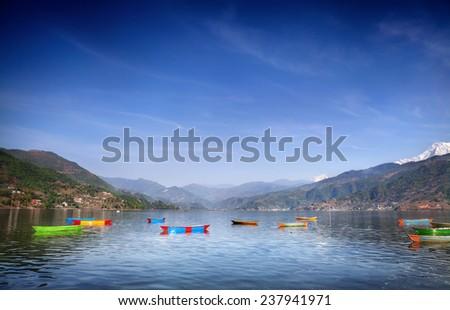 Colorful wooden boats on Fewa Tal at Himalaya mountains background in Pokhara, Nepal - stock photo