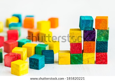 Colorful wooden building blocks on white table. Selective focus - stock photo